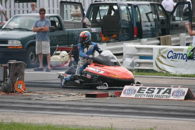 a person with a helmet on driving a racing vehicle